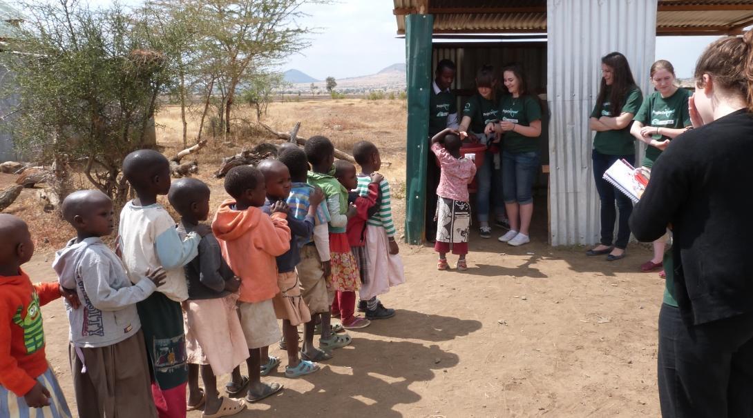Pasante revisa a niños durante brigada médica en Tanzania.